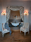 Two Baroque armchairs flanking free-standing bathtub in niche