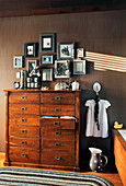 Gallery of pictures above wooden chest of drawers