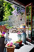 Blumen auf dem Fenstersims mit Blick auf die Terrasse mit Steinwand