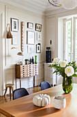 Blick vom Esstisch mit Blumen auf Schubladenschrank vor Bilderwand