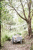Laid garden table and chairs under pennant chain in the garden with tall trees