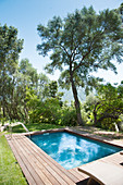 Swimming pool surrounded by wooden decking in Mediterranean garden