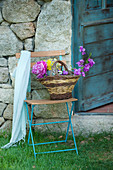 Basket of flowers on folding chair against stone wall