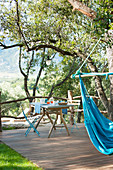 Blue hammock and set breakfast table on wooden terrace