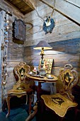 Antike Holzstühle und ein Tischchen vor der Holzwand im Chalet