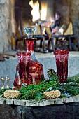 Rote Karaffe und Gläser mit Tannengrün vor offenem Kaminfeuer