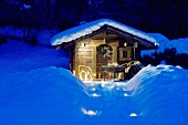 Lighted pathway leading to snow-covered, Alpine garden cabin