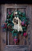 Festive wreath with tartan baubles and pine cones on wooden door