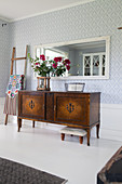 Old sideboard with decorative veneer below mirror on wall in living room