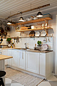 Ceiling lamps hung from branch and open shelving in country-house kitchen