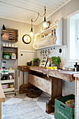 Old workbench below plate rack in country-house kitchen