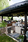 Outdoor kitchen with roof and rustic decorations