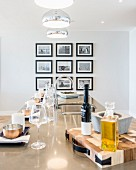 Place settings on long glossy dining table with gallery of pictures in background