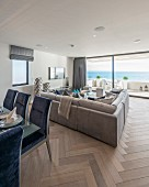 Blue upholstered dining chairs around table and pale sofa in front of glass wall in open-plan interior with sea view