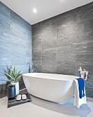 Designerbad mit frei stehender Badewanne, umgeben von Zimmerpflanze und Sektkühler