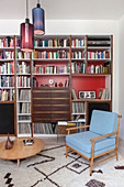 Retro armchair and round coffee table in front of bookcase with red back wall