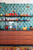 Colourful crockery in kitchen with wooden cupboards and blue retro wall tiles