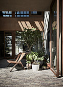Stuhl und Topfpflanzen auf Terrasse mit Kopfsteinpflastern