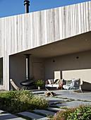Sonnige, überdachte Terrasse mit Sitzmöbeln und Hängekamin