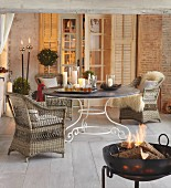 Wicker armchair at round table and fire in fire bowl