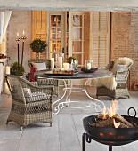 Korbsessel um runden Tisch und Feuer in Feuerschale