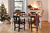Christmas tree and festively set dining table in period apartment