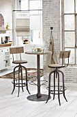 High, vintage table and two bar stools in front of brick wall in period apartment