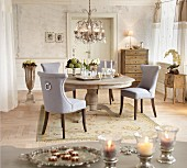Grey upholstered chairs around silver tray on round rustic table below chandelier in period apartment