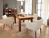 Cream armchairs around Advent arrangement on solid-wood table in modern interior