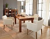 Naturweiße Armlehnsessel und massiver Edelholztisch mit adventlicher Dekoration in modernem Ambiente