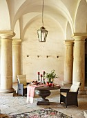 Armchairs and Advent arrangement on table below historical vaulted ceiling