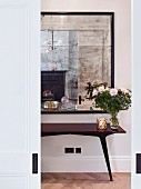 Old mirror above console table seen through sliding doors