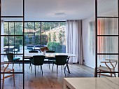 Dining room with glass wall leading to terrace and garden