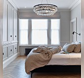 Chandelier and fitted wardrobes in elegant bedroom
