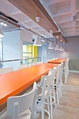 Orange tables in industrial-style canteen