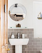 Round mirror and half-height tiled wall in bathroom with open door