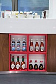 Various bottles of sauce in four square shelf compartments