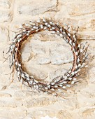 Wreath of artificial willow catkins hung on stone wall