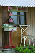 Hand-sewn fabric containers above folded fabrics on small table against rustic wooden façade