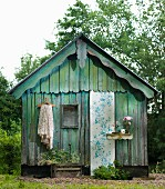 Weathered wooden hut decorated with strip of floral wallpaper, fabric and flowers