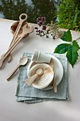 Various wooden cutlery, paper cups and bowls arranged on linen napkin