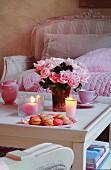 Romantisch gedeckter Couchtisch mit Rosenstrauß und Macarons