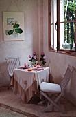 Romantisch gedeckter Tisch unter dem Fenster