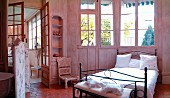 Metal bed and lattice window in French-style bedroom