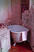 Free-standing bathtub behind floral screen