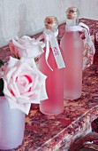 Labelled bottles and roses on pink marble surface