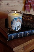 Lit candle in jar with angel motif on top of antique book
