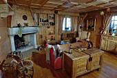Uriges Wohnzimmer im Landhausstil mit offenem Kamin und Kassettendecke