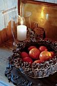 Mit Zapfen verzierter Korb mit Mandarinen neben einer Kerze