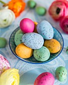 Colourful speckled eggs in bowl; Easter arrangement on pale blue tablecloth